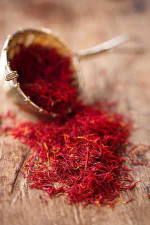 sieve: saffron spice in rustic sieve on old wooden background, closeup Stock Photo