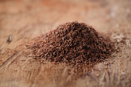 grated: pile of hot chocolate flakes  on wooden background, shallow DOF Stock Photo