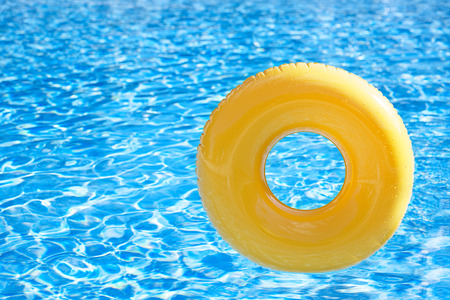 float tube: floating ring on blue water swimpool with waves reflecting in the summer sun
