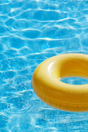 夏の太陽の下で反射波と青い水 swimpool のフローティング リング