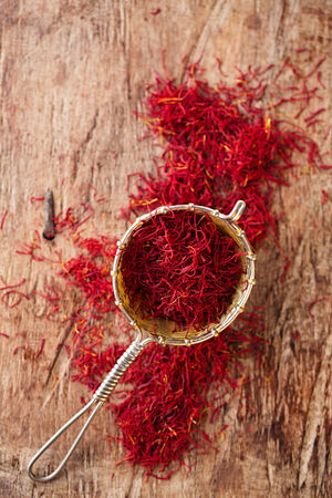 saffron spice in rustic sieve on old wooden background, closeup photo