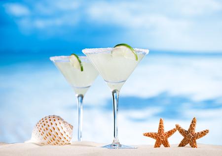 margaritas: margarita  cocktail on beach, blue sea and sky background