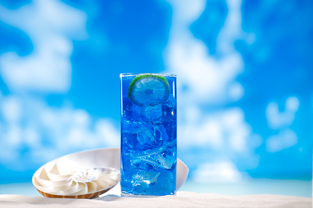 slush: blue slush ice in glass  on sea beach background