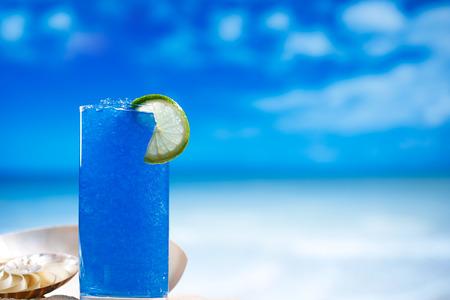 slush: blue slush ice in glass  on sea beach background