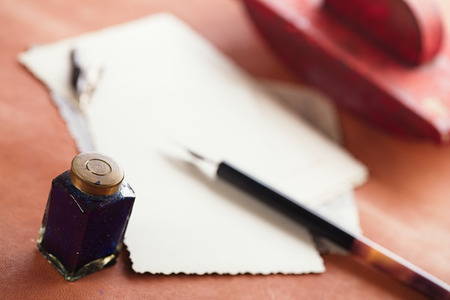 red pen: vintage red leather ink blotter  with retro post cards on leather table, shallow dof Stock Photo