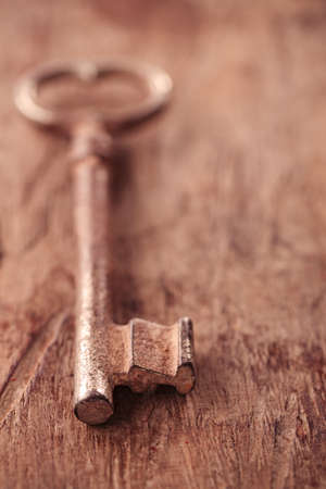 large and small rusty vintage metal keys on old wooden background, shallow dof photo