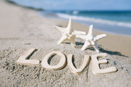 two starfish with love message on Florida beach  under the sun light, shallow dof photo
