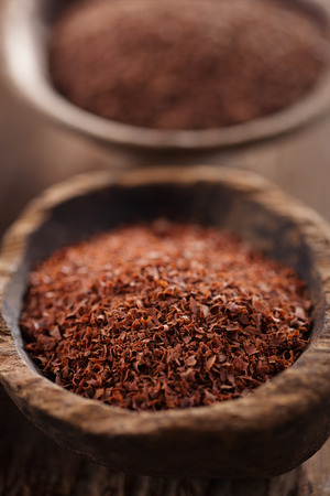 fine grated chocolate in old wooden spoon, shallow dof photo