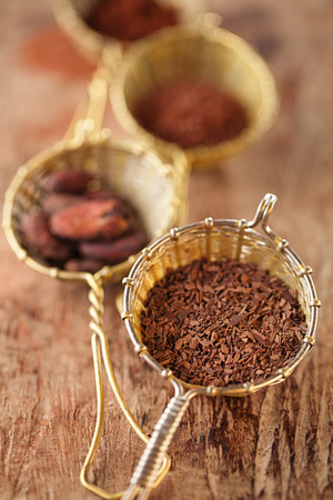 hot chocolate flakes with chilli flavor in old rustic style silver sieve, shallow dof photo