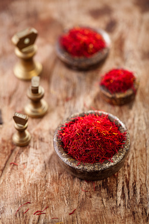 saffron spice in antique vintage iron bowls weights on wooden table photo