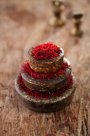 saffron spice in antique vintage iron bowls weights stacked on wooden table photo