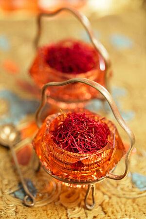 saffron spice in antique vintage glass bowl, closeup photo