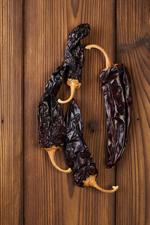 pepper flakes: chipotle - jalapeno smoked chil whole  on old textured wood Stock Photo