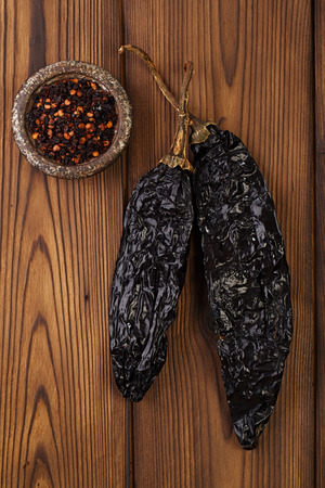 pepper flakes: chipotle - jalapeno smoked chili flakes,   and whole in iron weight bowl on old textured wood Stock Photo