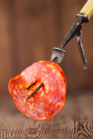slice of sausage chorizo on meat fork and wooden backdrop photo