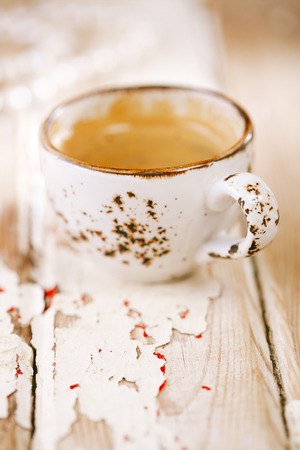 Coffee cup on old wooden table, shallow dof photo