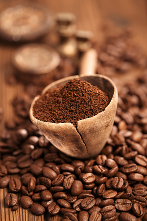 drying: grated coffee in spoon on roasted coffee  beans background Stock Photo
