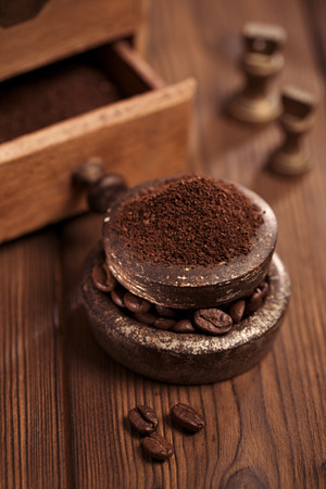 grated coffee in old iron weights and wooden  background photo