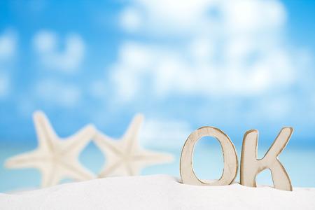 OK message with two starfish on Florida white sand beach  under the sun light, shallow dof photo