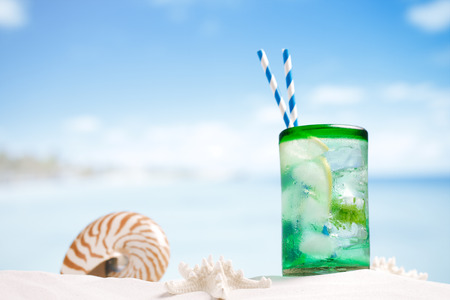 cocteles de frutas: cóctel mojito con hielo, ron, limón y menta en un vaso sobre la arena de playa y paisaje marino