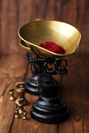saffron spice in antique vintage iron scale bowl  on wooden table, shallow dof photo