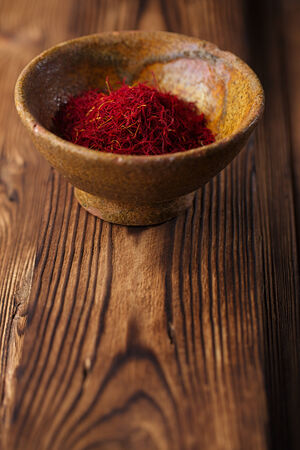 saffron spice in earthenware bowl on old textured wooden background, closeup photo