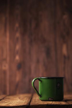 vintage green  enamel mug on old wood, shallow dof photo