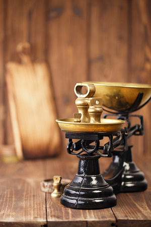 kitchen scale: Vintage cast iron kitchen  scale with weights on old wooden table Stock Photo