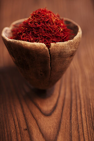 saffron spice in antique wooden spoon on old wood background, closeup photo