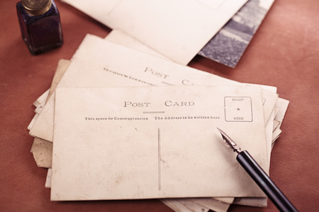 blotter: retro photo post cards , vintage ink , pen, blotter and camera on old leather table