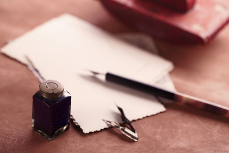 vintage red leather ink blotter  with retro post cards on leather table, shallow dof photo