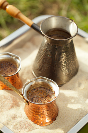 turk: coffee preparation in copper pot with hot golden sand outdoor, shallow dof