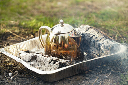 Making tea or coffee in the campfire on nature photo