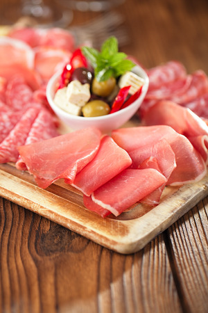 cold cuts: meat antipasti Platter of Cured Meat,   jamon, olives, sausage, salami  on old wooden board