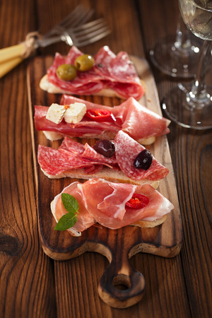 cured ham: Cured Meat and ciabatta bread on wooden board, white wine on background