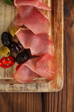 meat platter of Cured Meat and olives on old wooden board photo