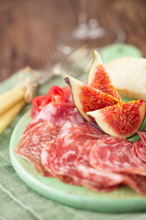 meat platter of Cured Meat and figs on green wooden board photo
