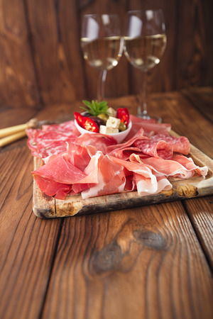 antipasti: antipasti Platter of Cured Meat,   jamon, olives, sausage, salami,  ciabatta and white wine glasses on textured wooden table Stock Photo