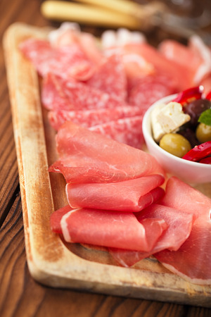 meat antipasti Platter of Cured Meat,   jamon, olives, sausage, salami  on old wooden board photo