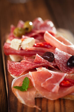 Cured Meat and ciabatta bread on wooden board, white wine on background