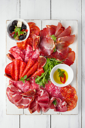 cured ham: antipasti Platter of Cured Meat,   jamon, sausage, salame  on textured white wooden table