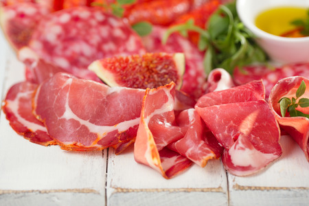 antipasti Platter of Cured Meat,   jamon, sausage, salame  on textured white wooden table photo