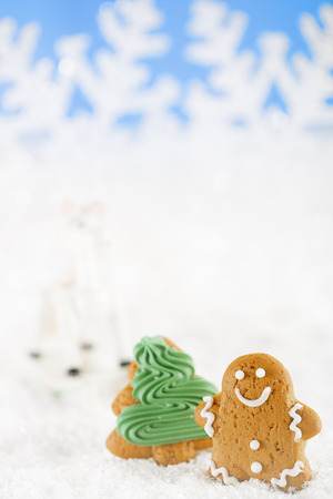 Gingerbread man and christmas tree  on a festive Christmas snow background, nice postcard photo