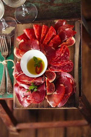 cured ham: wooden board of Assorted Cured Meats, olive oil, fork and glasses of white wine on vintage stool
