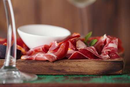 cured ham: wooden board of Assorted Cured Meats, olive oil and glasses of white wine on vintage stool