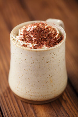 whipping: hot chocolat vintage mug, topping with cream and grated chocolate, shallow dof