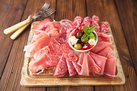 cold meal: antipasti Platter of Cured Meat,   jamon, olives, sausage, salami,  ciabatta and white wine glasses on textured wooden table Stock Photo
