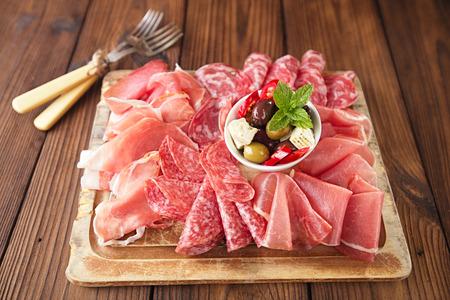Plato antipasti de Embutidos, jamón, aceitunas, chorizo, salami, ciabatta y copas de vino blanco de mesa de madera de textura