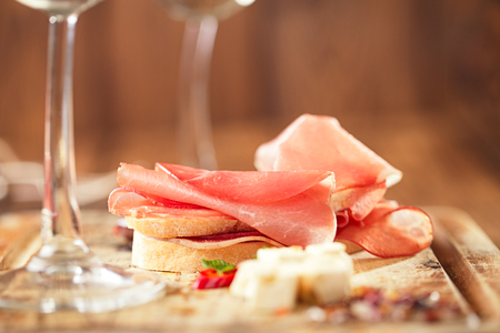 prosciutto: Cured Meat and ciabatta bread on wooden board, white wine on background