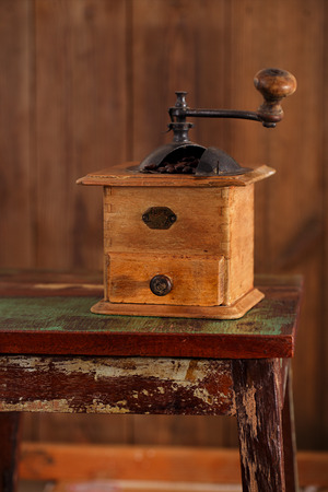 Nostalgic coffee grinder on old stool and textured wood background photo